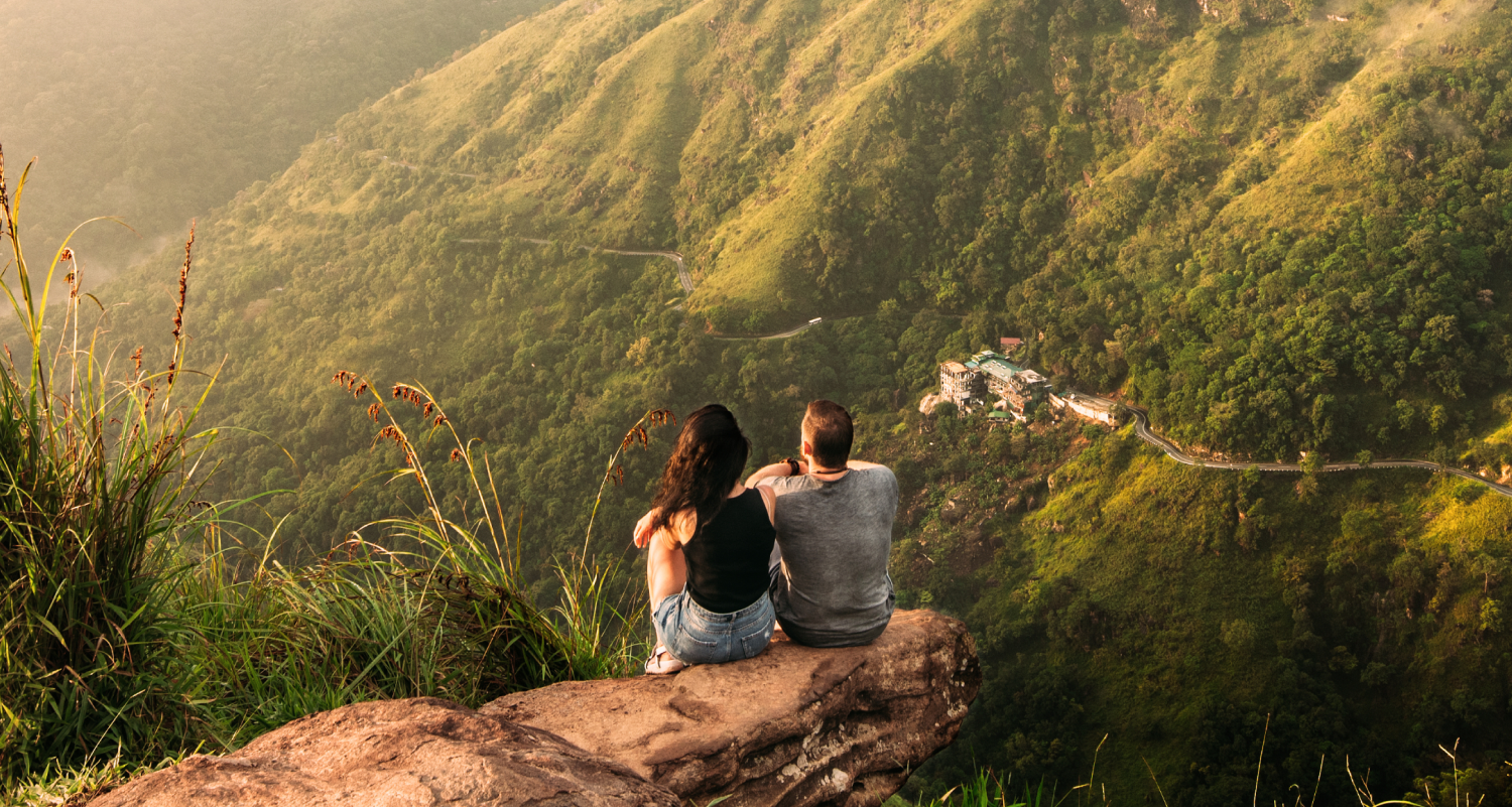 Couple sitting together on a mountain taking in the view.